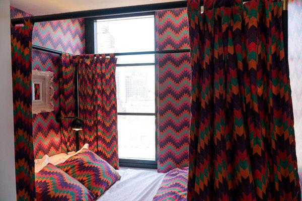 肯·富尔克在为西38街的亨利庄园设计单间公寓样板间时使用大量锯齿图案。四柱床的床帷与壁纸是配套的。