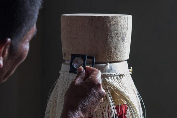 西蒙·埃斯皮納爾在檢查他的一頂傑作帽子上的編織。