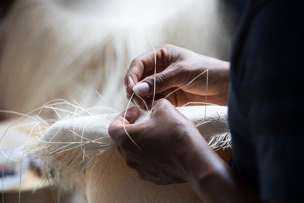 加布里埃爾•盧卡斯在他位於蒙特克里斯蒂的工作室裡,將一頂巴拿馬草帽中的一根稻草替換掉。