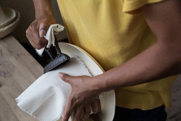 加布里埃爾·盧卡斯牢牢地用熨斗熨住一頂帽子,以幫助稻草保持其結構。