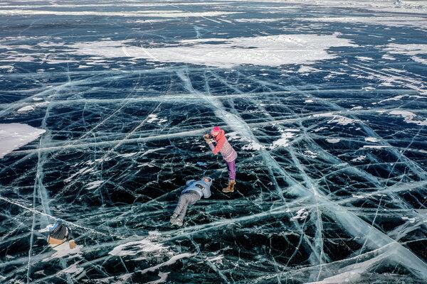 俄羅斯西伯利亞,遊客在貝加爾湖上潔凈的冰上拍照。